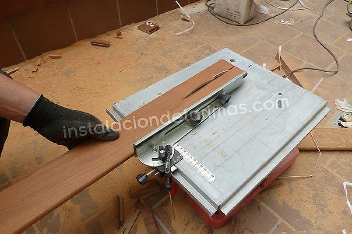 Foto de una sierra ingletadora en la que se está cortando transversalmente una tabla para el montaje en un muro recubierto con tarima.