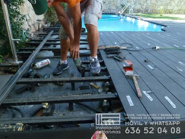 foto de instalador, entre los rastreles, instalando la tarima sintética de exterior alrededor de una piscina
