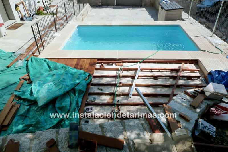 Foto de instalación de tarima exterior cubierta con una lona verde para proteger la madera de golpes o manchas durante la instación