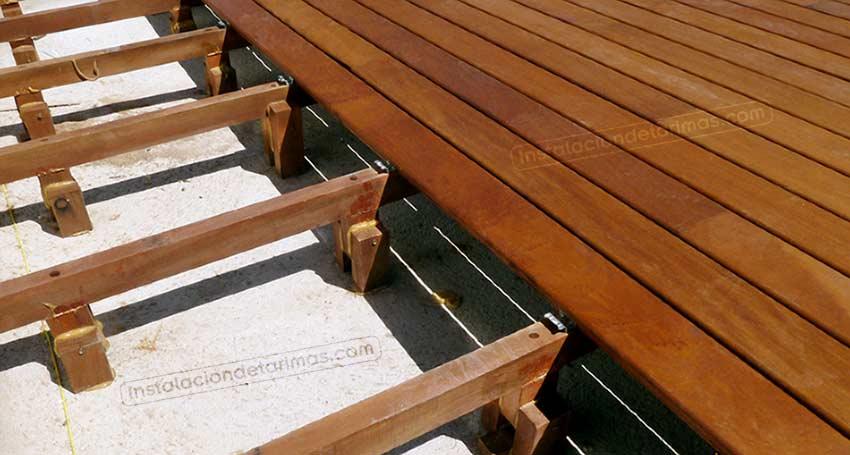 foto donde se observa la instalación de los rastreles elevados con patas de madera durante una instalación de tarima exterior